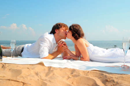 couple kissing while lying on the shore photo