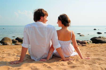 mujeres sentadas: Vista trasera de una pareja sentada en la playa Foto de archivo