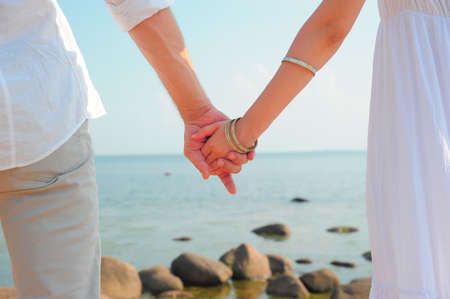 clasps: Detail of young couple holding hands on beach background  Stock Photo