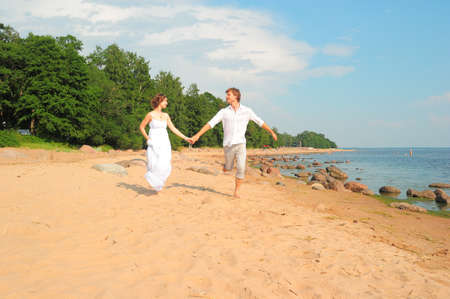 A young couple running on beach photo