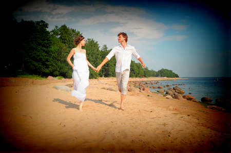 A young couple running on beach Stock Photo - 11422291