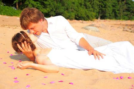 besos apasionados: pareja bes�ndose mientras est� acostado en la orilla