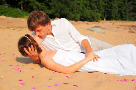gentle dream vacation: couple kissing while lying on the shore Stock Photo
