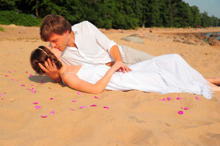 besos apasionados: pareja bes�ndose mientras se est� acostado en la orilla