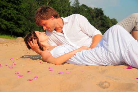 pareja bes�ndose mientras est� acostado en la orilla photo