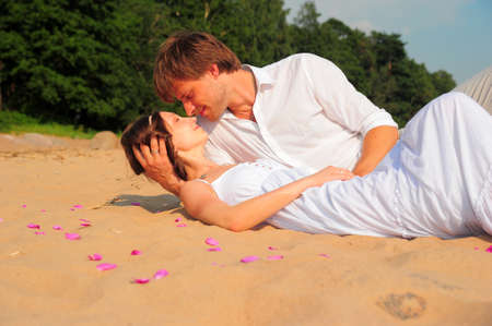 young couple hugging kissing: couple kissing while lying on the shore Stock Photo