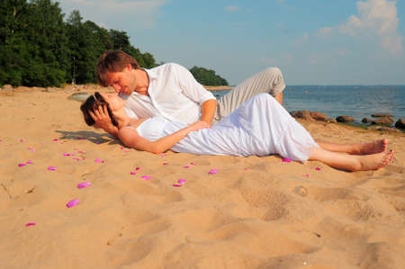 passionate embrace: couple kissing while lying on the shore Stock Photo
