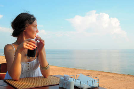 chica en un café junto al mar