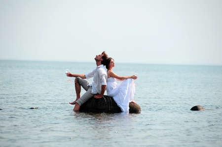 woman standing back: romantic pair on the seashore Stock Photo