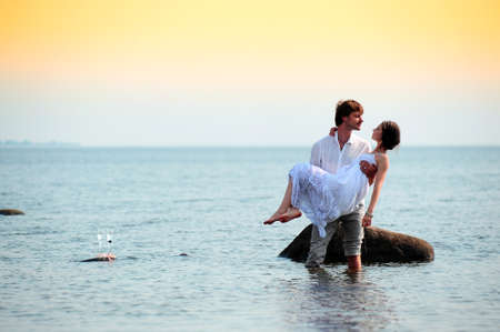 woman beach dress: Young happy couple having fun on the beach  Stock Photo