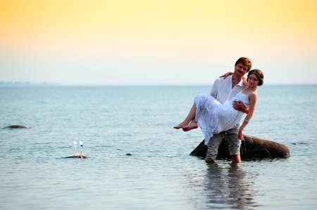 honey moon: young romantic pair walks at water