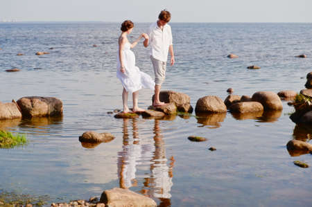 young romantic pair walks at water photo