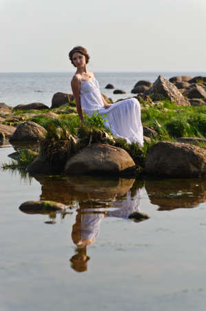 young woman in white dress sitting on the rocks near the water photo