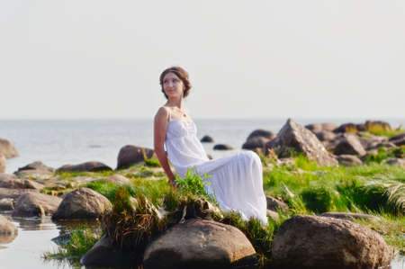 gentle dream vacation: young woman in white dress sitting on the rocks near the water
