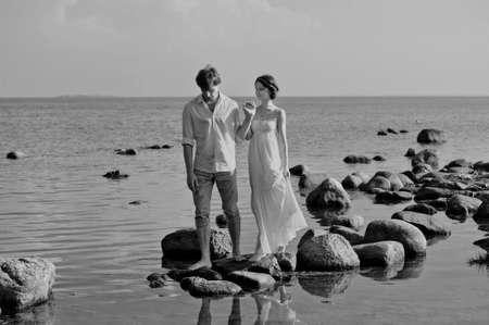 young romantic pair walks at water photo