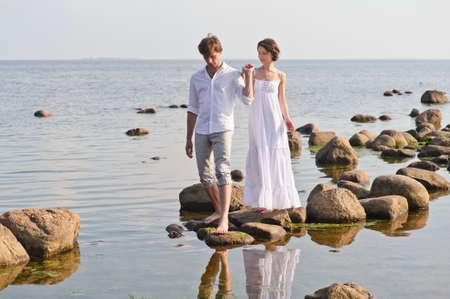 femme romantique: jeune couple romantique marche à l'eau