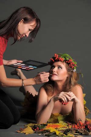 make-up stylist past het model in de studio Stockfoto - 11866870