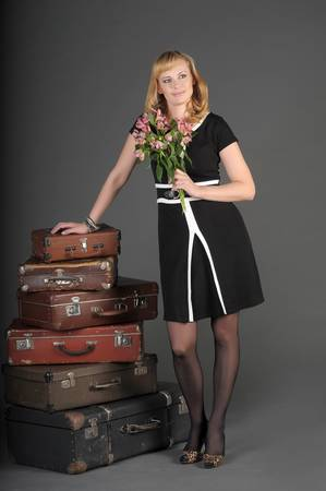 young woman and a lot of old suitcases photo