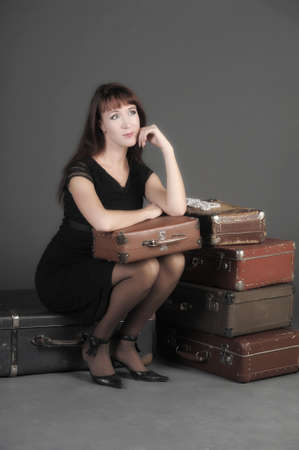 young woman and a lot of old suitcases Stock Photo - 11420858