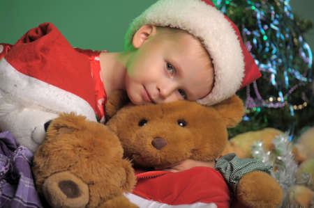boy in the Christmas hat with toy bear photo