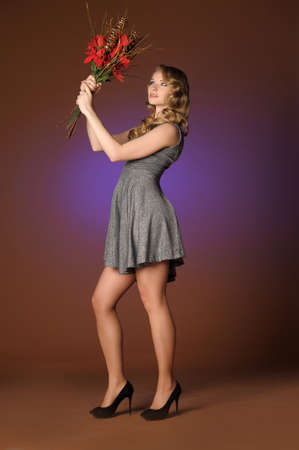 Vintage attractive blonde woman with a Christmas flower Stock Photo - 13572021