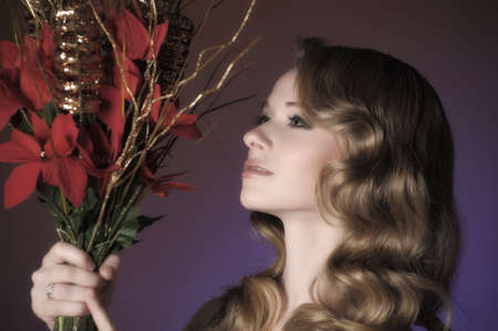 Vintage attractive blonde woman with a Christmas flower Stock Photo - 13571919