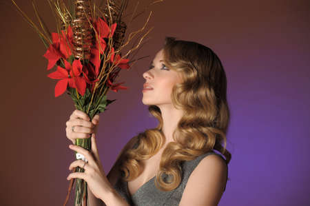 Vintage attractive blonde woman with a Christmas flower Stock Photo - 13571924
