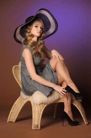the beautiful young girl in a big hat in studio photo