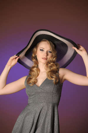 Fashion girl in a big hat in the studio  photo