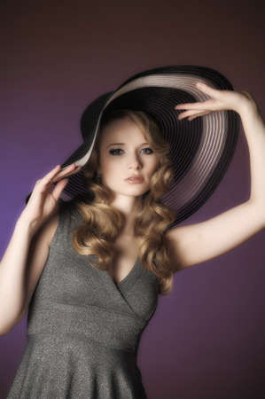 Fashion girl dans un grand chapeau dans le studio photo