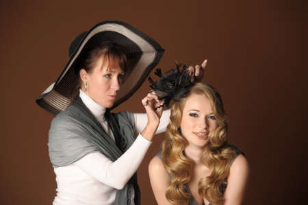 The stylist corrects models a hairdress in studio on shooting photo
