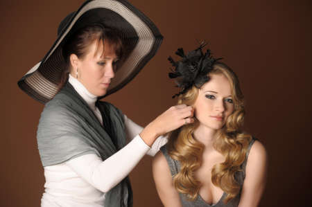 The stylist corrects models a hairdress in studio on shooting Stock Photo - 12377221