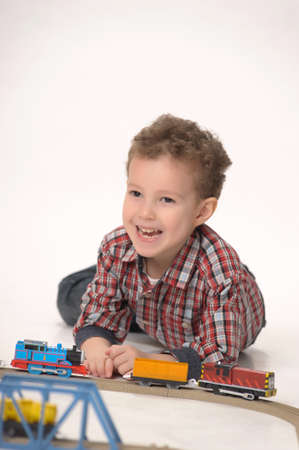 Boy playing with toy railroad photo