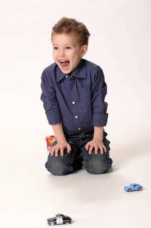 sitting on floor: boy playing with cars Stock Photo
