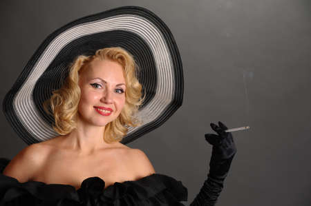 elegant woman in a hat smoking photo