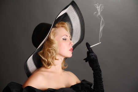 bonnet up: elegant woman in a hat smoking Stock Photo