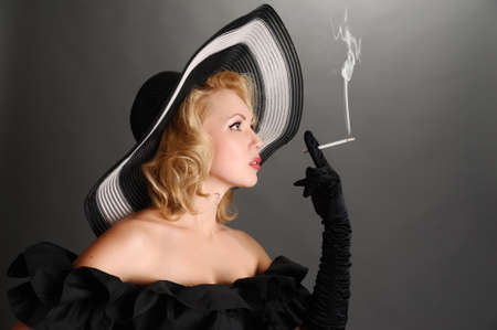 brown leather hat: elegant woman in a hat smoking Stock Photo