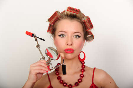 haircurlers: A housewife with hair-curlers and with a magniglass