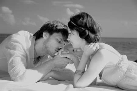 passionate embrace: Young romantic couple on the beach, sepia tone