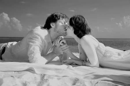 besos apasionados: Pareja joven rom�ntica en la playa, en tonos sepia