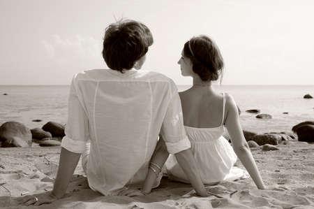 Young romantic couple on the beach, sepia tone photo