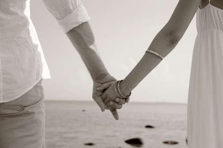 verlobt: Detail der jungen Paar Händchen haltend am Strand Hintergrund, Sepia