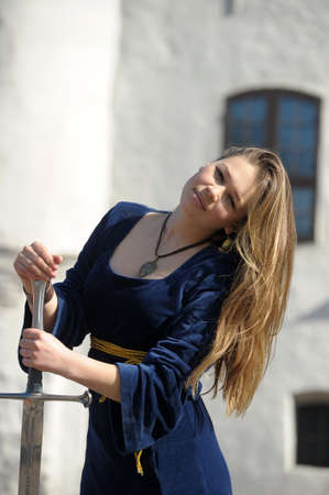 young beautiful woman in medieval dress with a sword in the hands of photo