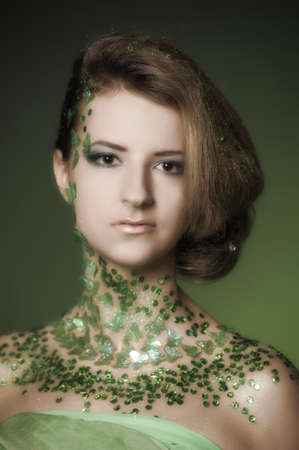 the beautiful girl with a creative make-up with spangles photo
