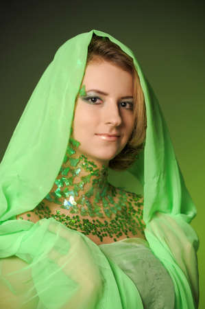 the girl in a green hood with spangles on a neck in the form of an ornament photo