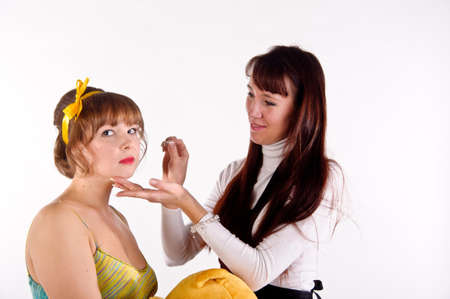 stylist working with the model in the studio before shooting photo