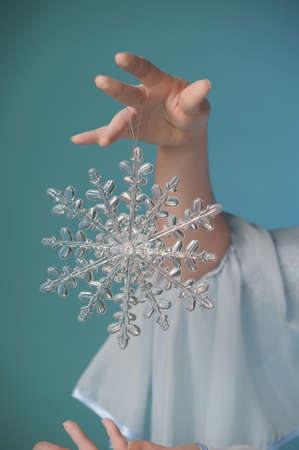 Woman hand holding big holiday snowflake photo