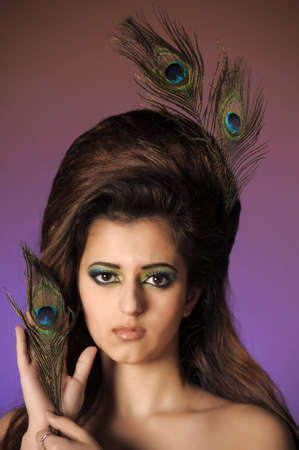 Portarit of beautiful young girl with peacock feather Stock Photo - 13281001
