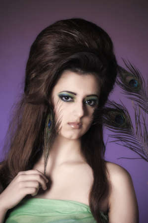 Portarit of beautiful young girl with peacock feather Stock Photo - 13280992