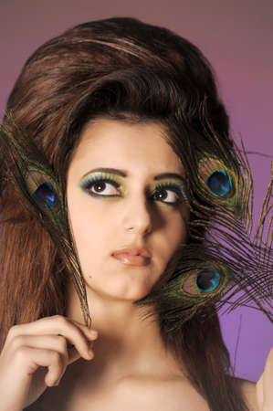 Portarit of beautiful young girl with peacock feather Stock Photo - 13281012